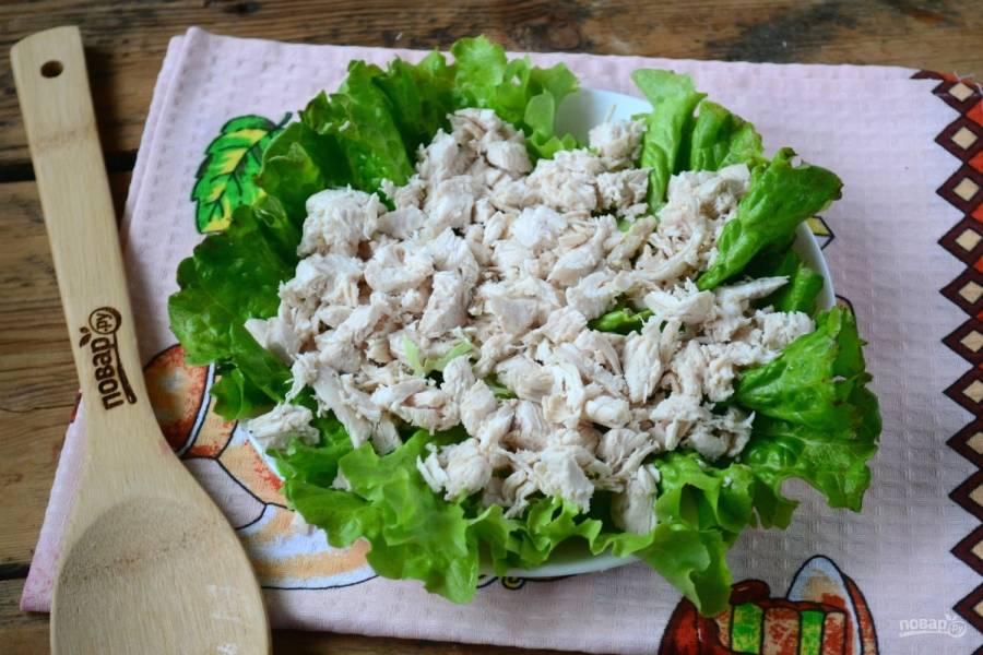 Куриную грудку мелко порежьте и положите на дно плоской тарелки, по желанию её можно украсить листьями салата.