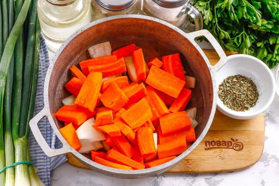 Морковь нарежьте крупными кусочками или брусочками, добавьте в емкость и обжарьте вместе с луком на умеренном нагреве примерно 4-5 минут до румяности.