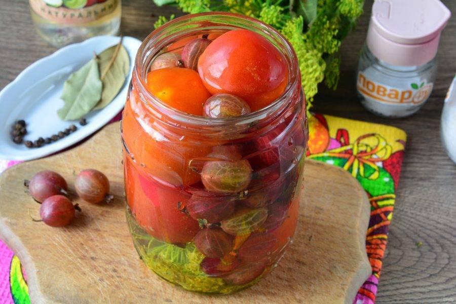 Заполните банки помидорами и крыжовником, залейте овощи кипятком и оставьте на 10 минут.