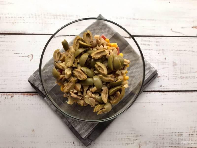 Оливки разрежьте на несколько частей и высыпьте в тарелку.