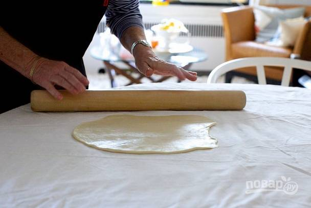 5. Включите духовку, пусть разогревается до 180 градусов. Рабочий стол застелите чистой салфеткой или пергаментом, например. Выложите тесто и начните раскатывать.