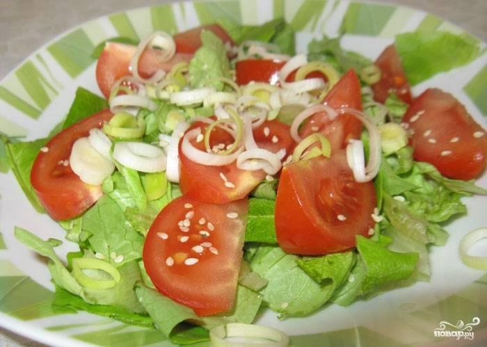 Помидоры вымыть и нарезать крупными дольками.  Смешать салат, помидоры, порей и кунжут.