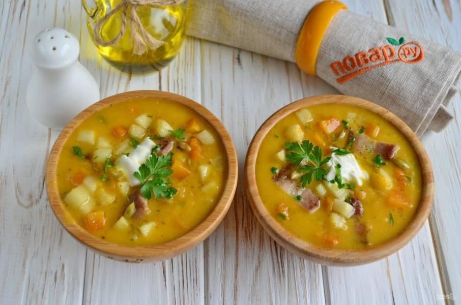 Разлейте суп по тарелочкам, добавьте жареные кусочки бекона, яблоки и  тыкву. Положите по ложечке сметаны и подайте к столу. Приятного аппетита!