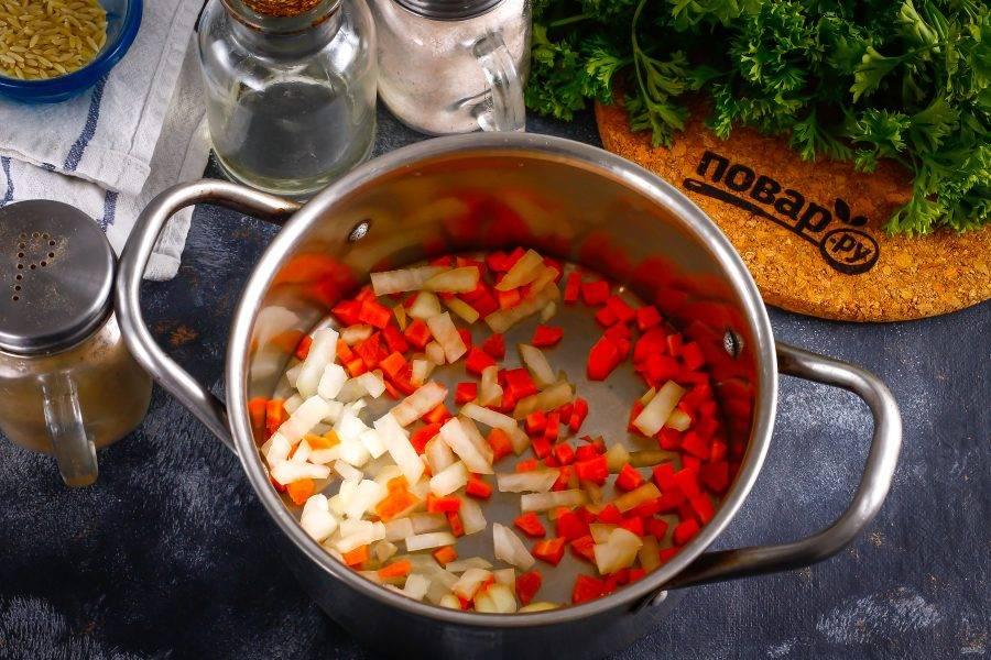 Нарежьте мелкими кубиками репчатый лук и морковь. Отпассеруйте в кастрюле на растительном масле примерно 2-3 минуты до легкой румяности.