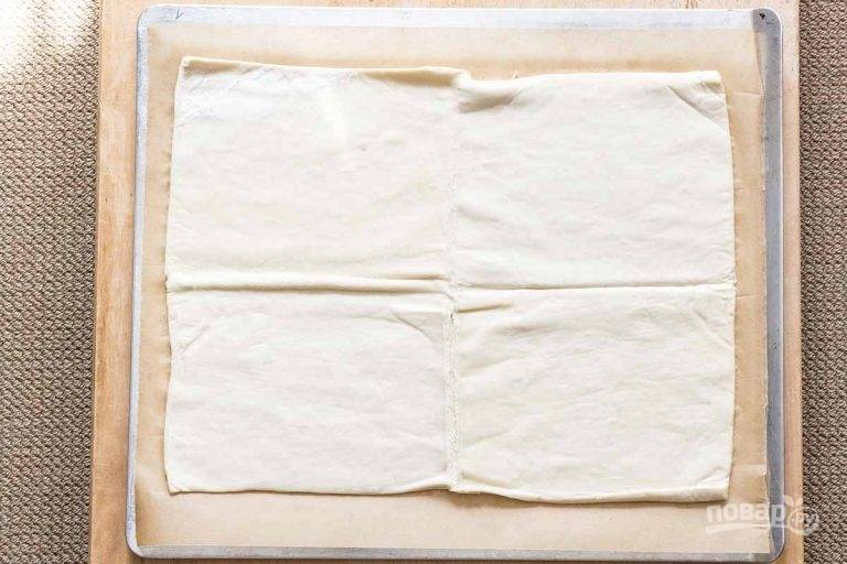 1.Разверните слоеное тесто и заранее его разморозьте. Выложите тесто на пергамент и раскатайте его тонко, но не слишком.