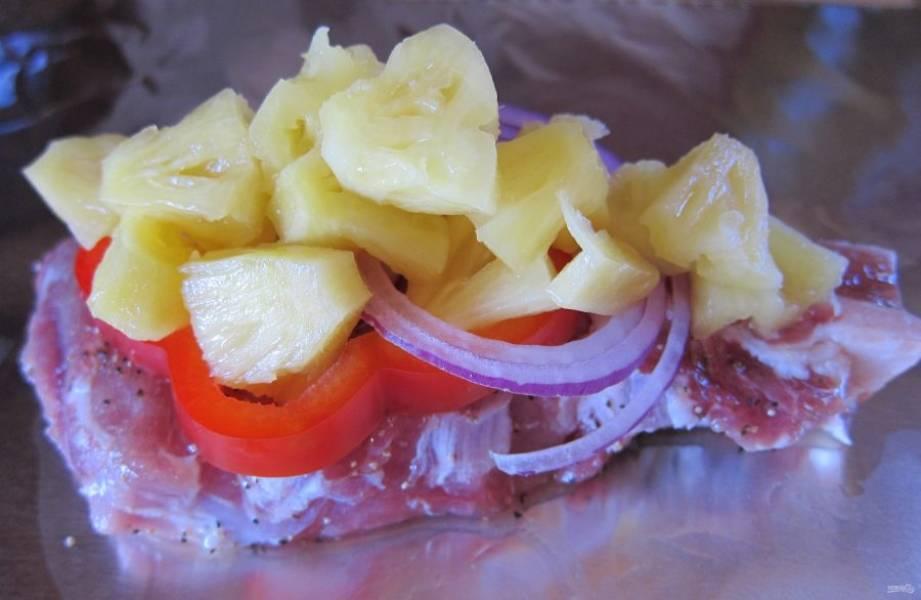 Подготовьте 4 кусочка фольги. На каждый положите по кусочку мяса, посолите, поперчите. Выложите по паре колечек лука, колечко перца и кусочки ананаса на каждую порцию.