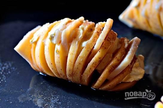 Сыр  пармезан и сливочное масло порежьте тонкими дольками и вставьте в разрезы на картошке. Посолите картошку и посыпьте сушеным чесноком.
