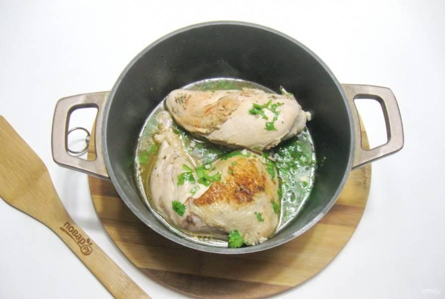 Налейте 100-150 мл. воды. Добавьте чеснок и петрушку. Накройте казан крышкой и тушите курицу на небольшом огне 20-25 минут до готовности.