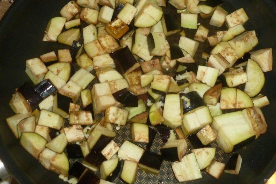 Сначала приготовим баклажаны. На сковороде разогрейте половину масла и выложите небольшими кубиками нарезанные баклажаны, добавьте через пресс пропущенный чеснок. Жарьте баклажаны, помешивая, до золотистой корочки.