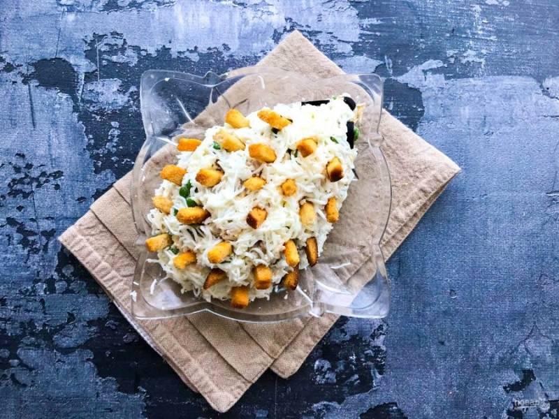Украсьте салат оливками и сухариками.