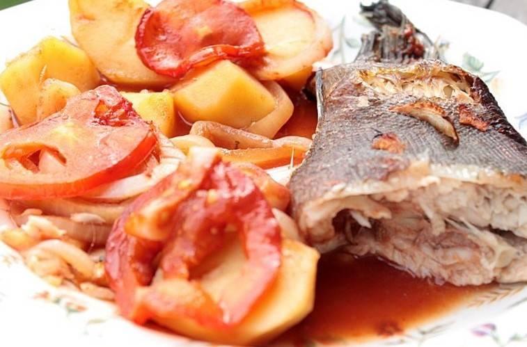 """2. На дно формы выложите """"подушку"""" из картофеля (лучше его порезать кружочками), а по бокам рыбы - лук кольцами и помидоры. прикройте фольгой рыбу и поставьте в разогретый до 200 градусов духовой шкаф на тридцать минут. За десять минут до готовности снимите фольгу. Это нужно для того, чтобы рыба покрылась корочкой."""
