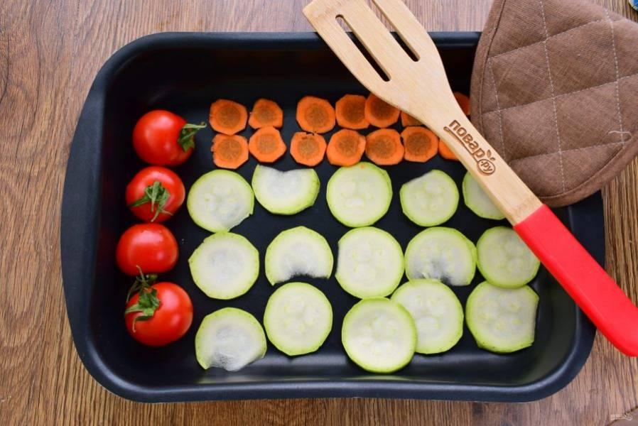 Кабачок, морковь и помидоры вымойте. Кабачок и морковь очистите, нарежьте тонкими кружками. Овощи разместите на противне, сбрызните оливковым маслом и поставьте в разогретую до максимума духовку на 15 минут.