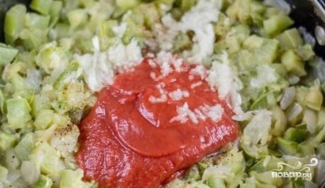 Добавьте томатную пасту, соль, черный перец и давленый чеснок. Все перемешайте и тушите 3-4 минуты.