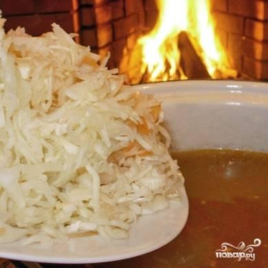 Вновь доводим до кипения, сразу после чего добавляем в суп квашеную капусту с небольшим количеством рассола. Варим еще 10-20 минут до желаемой кондиции капусты - одни любят помягче, другие потверже. Минут за 5 до окончания приготовления регулируем на соль и перец, добавляем по вкусу зелень и измельченный чеснок, если хотим - возвращаем в суп мясо, на котором варился бульон.