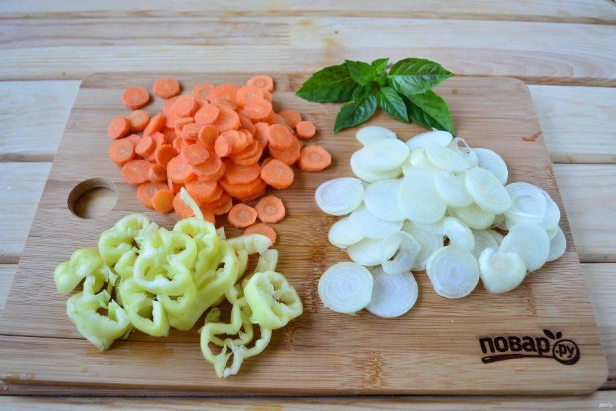 Лук нарежьте кружочками и разделите на кольца, морковь нарежьте кружочками, перец очистите от семян и плодоножки и нарежьте колечками или полукольцами.