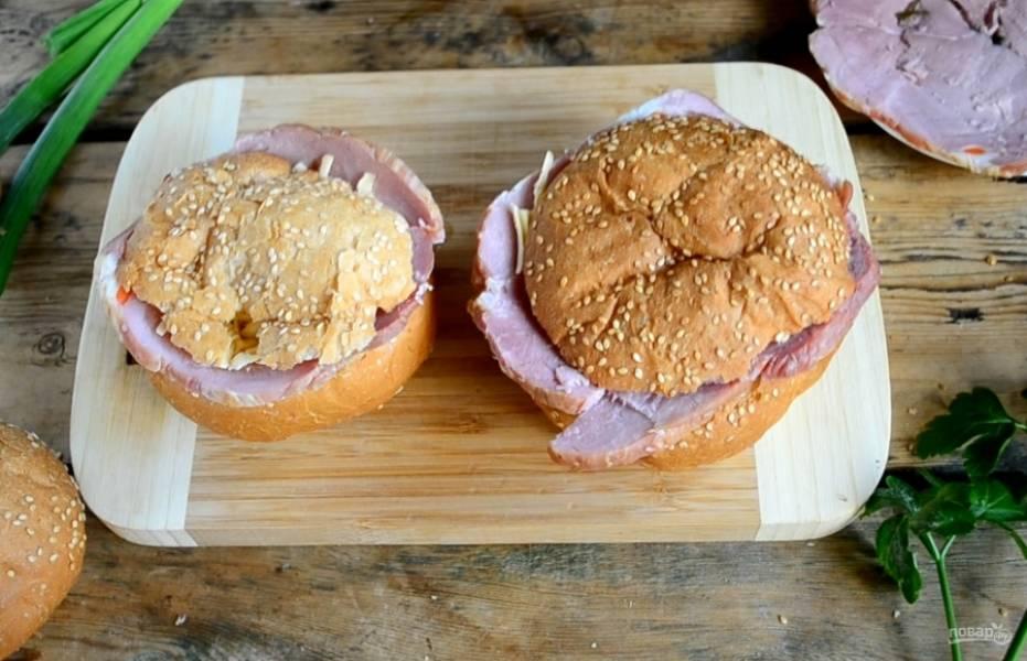 Сыр натрите на крупной терке, присыпьте им сверху яйцо. Накройте верхом булочки.