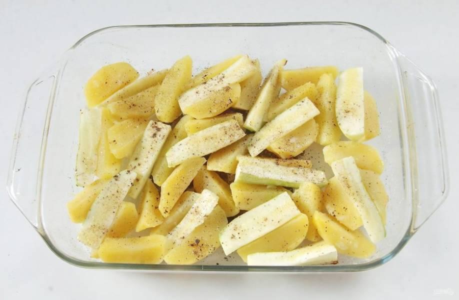 Кабачок разрежьте пополам и каждую поливину еще на 4-6 частей. Распределите кабачки между картофелем, сбрызните овощи маслом, посыпьте солью и специями.