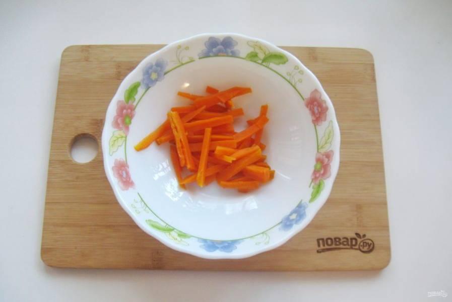Морковь отварите до готовности. Охладите, очистите, нарежьте соломкой и выложите в салатник.
