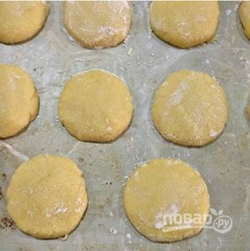 Уложите заготовки на противень и приплюсните их, придавая плоскую форму будущим печенюшкам.