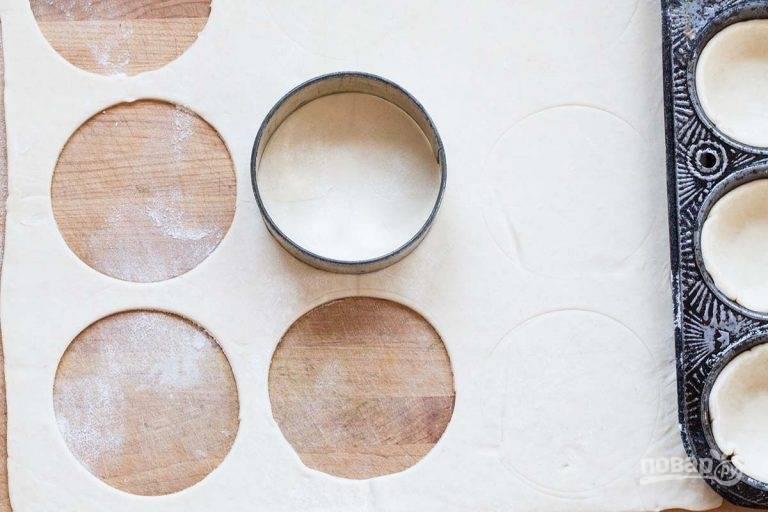 3.Разморозьте слоеное тесто, затем раскатайте его тонко и вырежьте кружочки. Уложите каждый в форму для выпечки кексов.