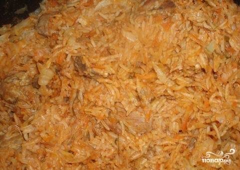 8.Измельченную капусту также добавляем в сковороду к тушеным ребрышкам и овощам. Солим, перчим по вкусу. Можно добавить любимые специи на собственное усмотрение. Перемешиваем все и продолжаем тушить на среднем огне, периодически помешивая.