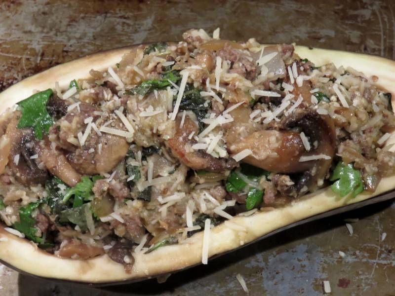 Раскладываем приготовленную начинку по половинкам баклажана, посыпаем все сверху остатками сыра.