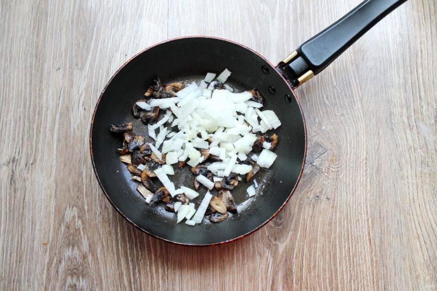 Репчатый лук почистите и мелко порежьте. Добавьте его в сковороду с обжаренными грибами, посолите.