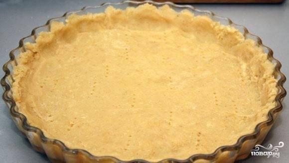3. Возьмите низкую форму. Смажьте ее дно и боковины маслом. Выложите в нее тесто. Аккуратно разровняйте пальцами так, чтобы толщина коржа была не более 1 см. Вилкой сделайте проколы по всему пласту.