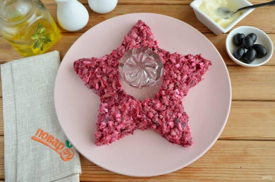 Возьмите круглую тарелочку, в центр поставьте стакан, это место для свечи. Вокруг выкладывайте салат, формируя звезду.