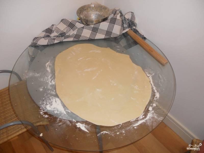 Посыпьте столешницу мукой и раскатайте на неё тесто, получится большой блин высотой и 0,5 см.