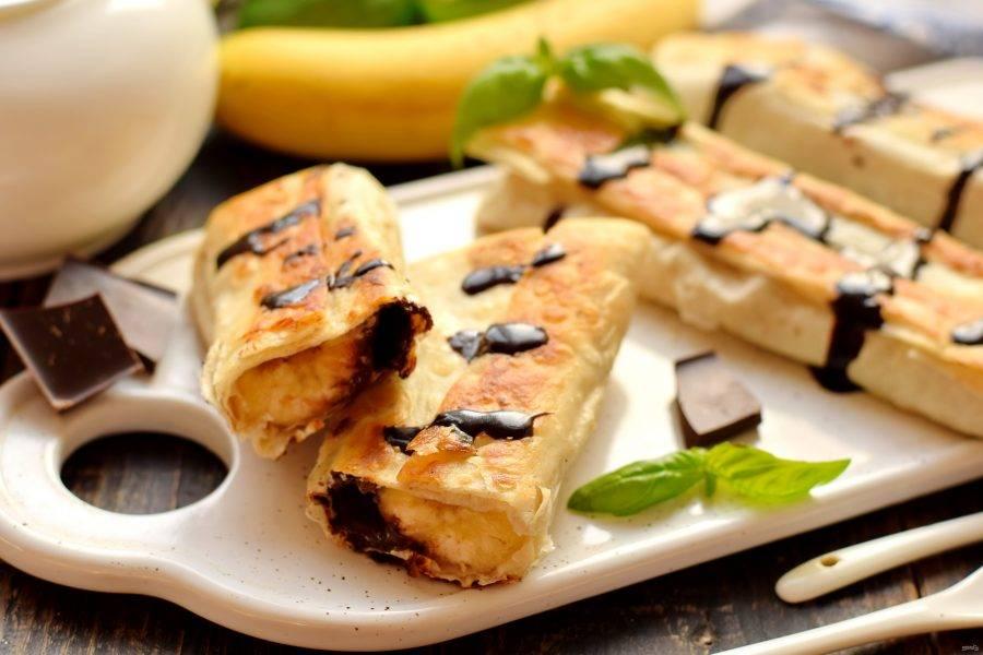 После жарки банан с шоколадом в лаваше выложите на салфетку, которая уберет верхний маслянистый слой. Рулеты при подаче можно полить шоколадом.