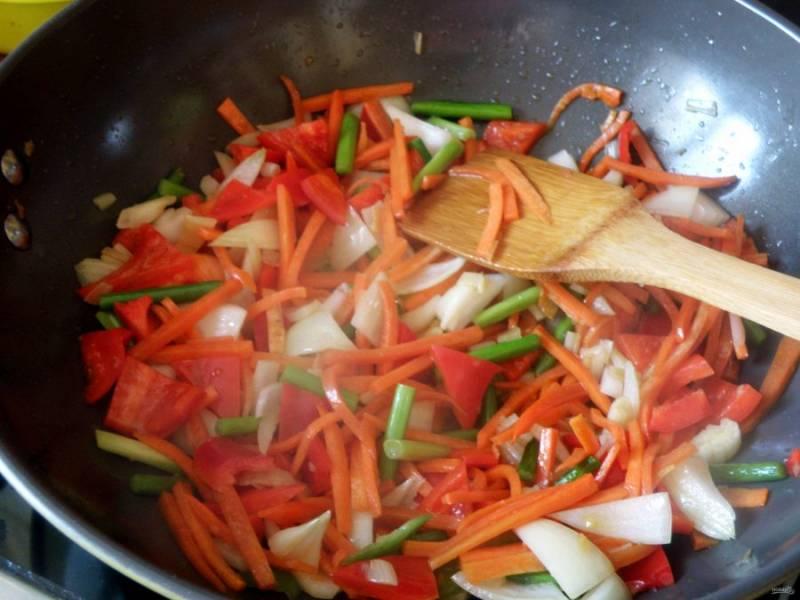 Пожалуй, самое главное в технике стир-фрая – это аккуратная равномерная нарезка. Хорошенько наточите нож и начинайте. Нашинкуйте лук и сладкий перец уголками, морковь – тонкой соломкой, черешки сельдерея нарежьте тонкими ломтиками, а стрелки чеснока – кусочками длиной  в 3 сантиметра. Имбирь мелко нарубите. В воке раскалите растительное масло, опустите имбирь. Сразу же следом выложите подготовленные овощи и жарьте, помешивая и встряхивая вок, пару минут.