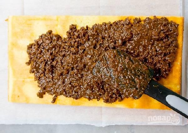 30. Корж разрежьте на 3 части. На одну выложите пасту пралине с шоколадом, распределите ее ровным слоем. Отправьте в холодильник на 15 минут.