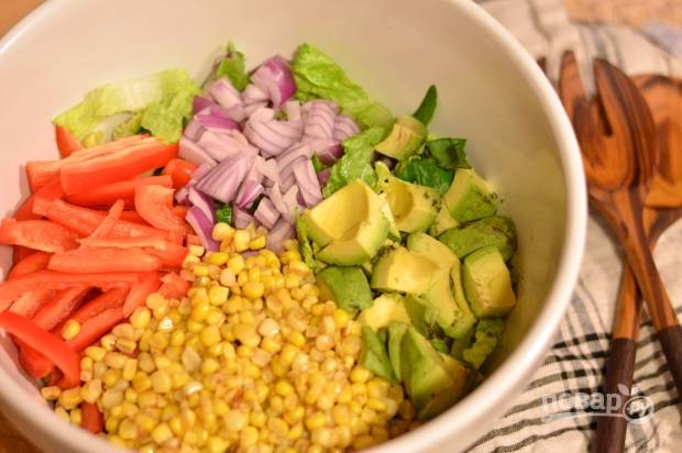 2. В глубокий салатник выложите измельченный лук, кукурузу (отварную или консервированную), нарезанный зеленый салат, перец и мякоть авокадо.