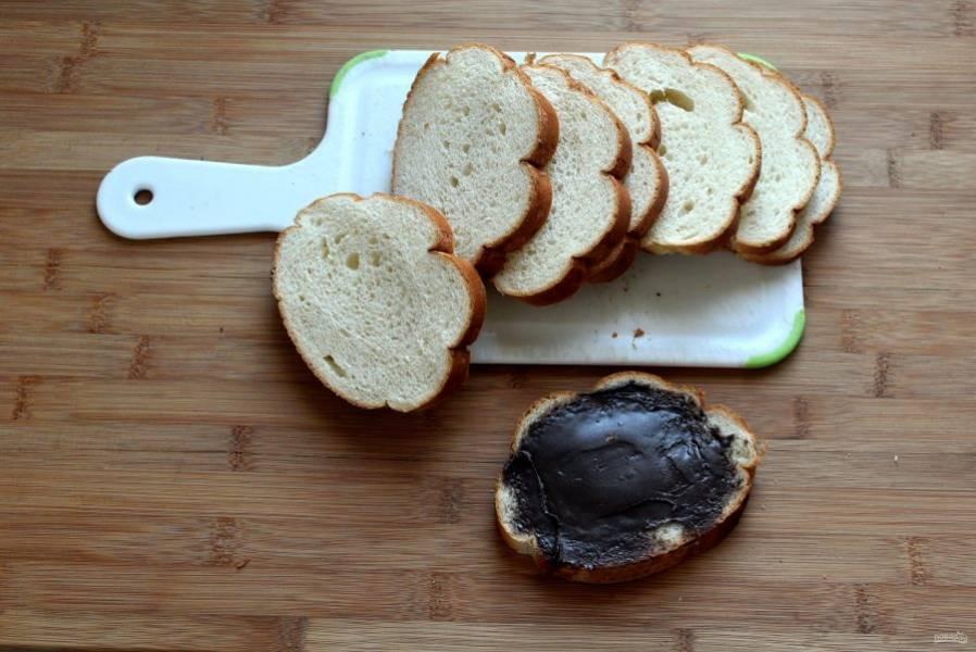 Нарежьте батон ломтиками толщиной в 1см. Смажьте одну сторону шоколадной пастой и накройте вторым ломтиком.