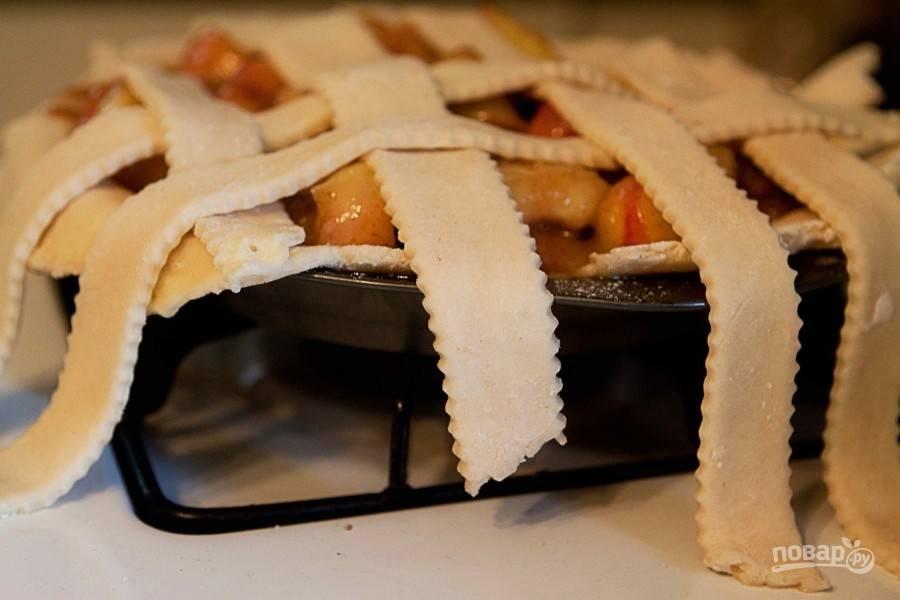 Переместите персиковую начинку в форму, а сверху красиво выложите полоски из теста, формируя решетку. Края обрежьте и смажьте пирог взбитым яйцом.