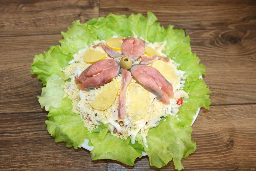 Украсьте верх салата кусочками рыбы и ломтиками лимона.