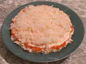 Лук мелко нарезать, залить кипятком и дать настояться в течении 5-10 минут для удаления горечи. Сверху на морковь положить лук, на лук - картофель, немножко посолить и смазать майонезом.