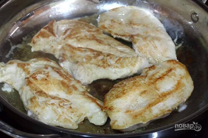 1.Вымойте мясо, разрежьте куриную грудку на 2 части. Разогрейте сливочное масло и выложите мясо, обжарьте его с двух сторон до золотистой корочки, переложите мясо в тарелку.