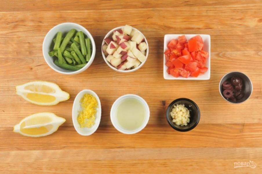 1. Подготовьте ингредиенты. Нарежьте небольшими кубиками помидор и картофель. Оливки нарежьте кружками. Чеснок измельчите. Фасоль разделите на половинки. С половины лимона натрите цедру и выжмите сок, вторую часть разрежьте на 2 дольки.