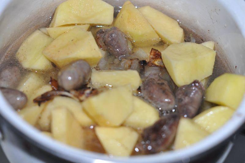 Чистим картофель и нарезаем его на небольшие кусочки, выкладываем в кастрюлю и заливаем стаканом воды. Добавляем к картофелю обжаренные сердечки и лук, накрываем кастрюлю крышкой и тушим все на медленном огне.