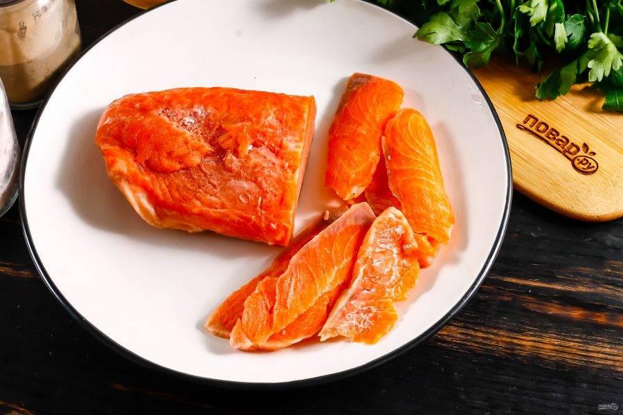 Кусочек замороженного лосося оставьте буквально на 5 минут при комнатной температуре, затем напилите острым ножом тонкие лепестки филе.