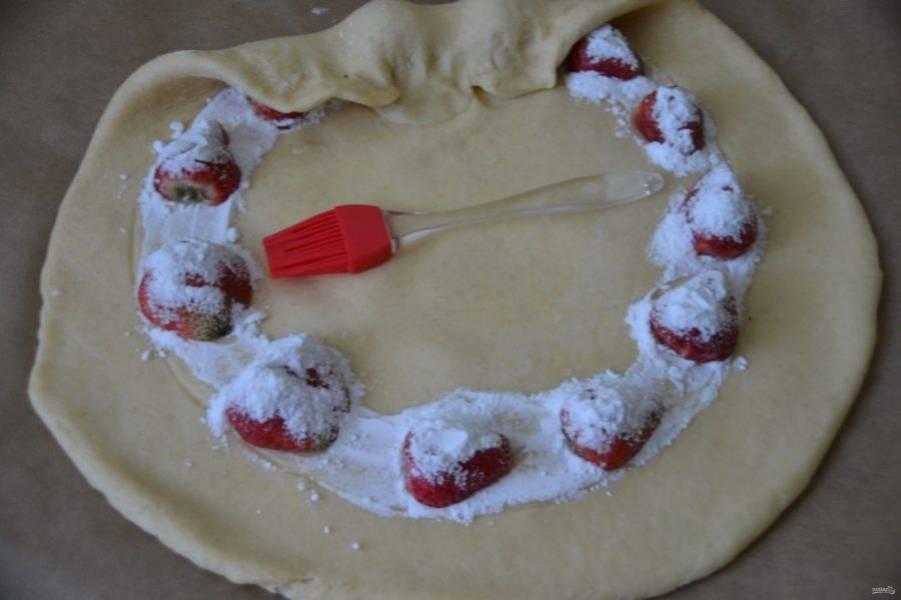 Выложите ягоды клубники на расстоянии примерно 1-1,5 см. друг от друга по кругу, сверху тоже присыпьте смесью сахарной пудры и крахмала, оставшимся белком промажьте внутренний круг, оберните ягоды наружным краем теста и закрепите. Если ягоды крупные, их можно разрезать пополам.