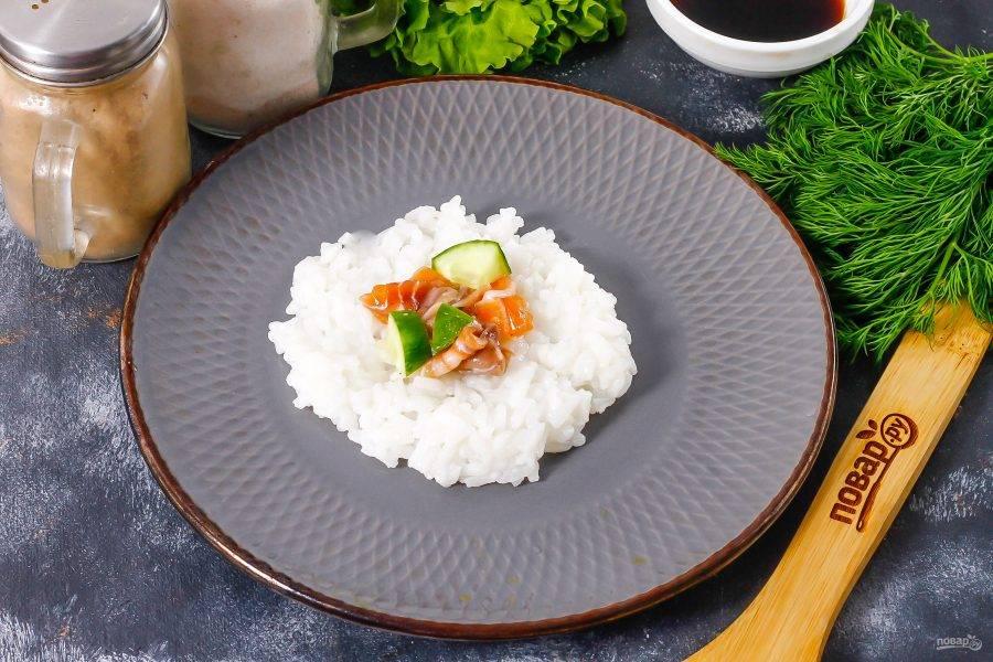 Нарежьте семгу кусочками, огурец промойте и нарежьте кусочками. Выложите в середину рисовой лепешки. Можно добавить немного сливочного или плавленого сыра.