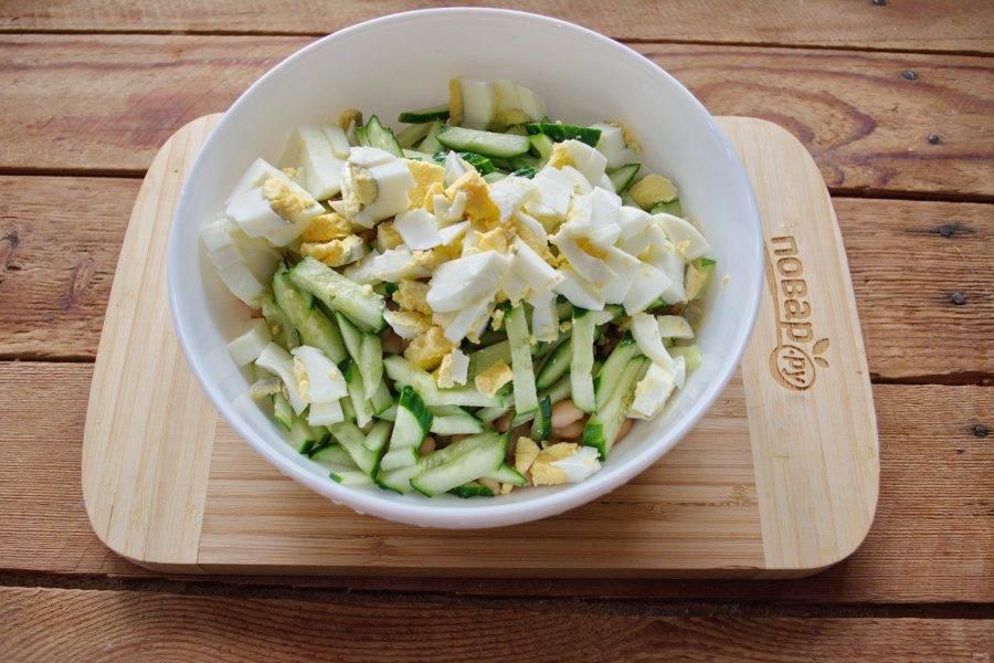 Отварите куриные яйца вкрутую. Охладите и очистите. Нарежьте произвольно. Вместо куриных можно использовать перепелиные яйца. Они в несколько раз меньше куриных. Их можно просто разрезать пополам и половинками добавить в салат.