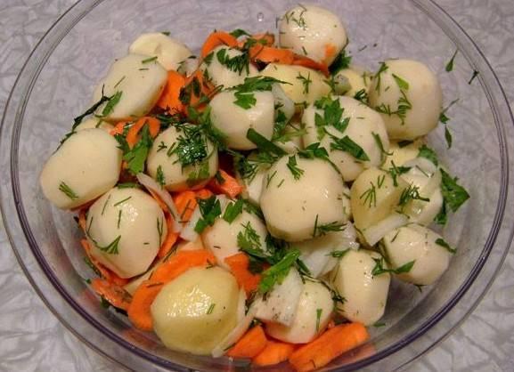 Картофель чистим и нарезаем на небольшие кусочки, если картошка небольшая, как у меня, то ее можно запекать целой. Выкладываем картофель в глубокую миску, добавляем морковку и лук, а также измельченную зелень, солим все и перемешиваем.