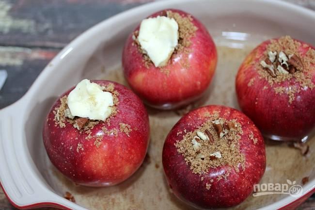 3. Добавьте на дно противня воды столько, чтобы только покрылось дно. К каждому яблочку добавьте кусочек сливочного масла сверху.