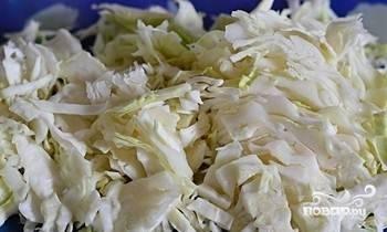 Затем нашинкуйте капусту. Отправьте её в суп. Добавьте лавровый лист и перец. Доведите бульон до кипения. Потом уменьшите огонь. Варите 15 минут под крышкой.