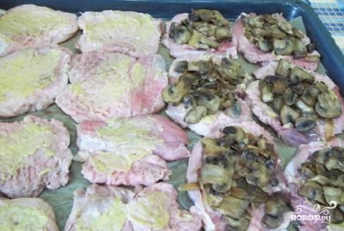 Помидоры нарезаем полукольцами, сыр натираем на крупной терке, чеснок мелко рубим. На этом подготовительные работы окончены. Приступаем к запеканию мяса. Противень застилаем пергаментом для выпечки. Выкладываем отбивные, приправляем сверху перцем и солью, а затем на каждый кусочек кладем жареные грибы.