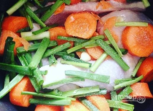 В глубокую емкость выложите лук и морковь. Окорочка вымойте, удалите остатки перьев и переложите их в миску к овощам. Добавьте очищенный и нарезанный чеснок, соль и кунжутное масло. Перемешайте все руками.